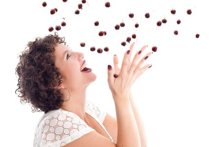 Pretty brunette with curls catching a drop of cherries photo