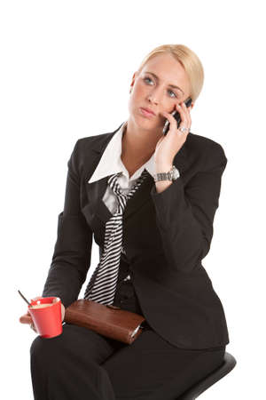 Attractive young business woman sitting and listening to the phone photo