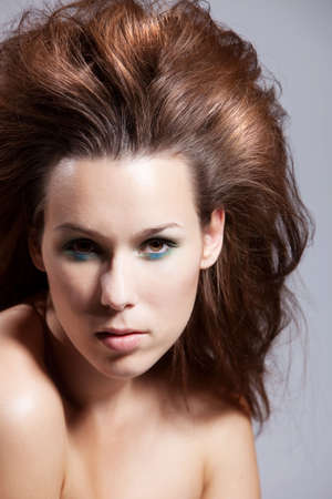 wild hair: Bella bruna dai capelli selvaggi su sfondo grigio
