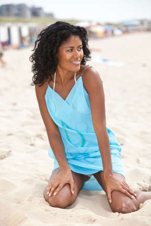 Beautiful brazilian girl sitting in the sand on the beach