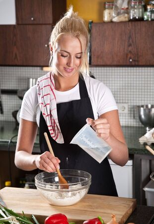 Pretty female chef adding water to the flour Stock Photo - 5609245