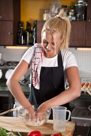 Beautiful young chef getting her hands dirty by mixing the dough Stock Photo - 5609254