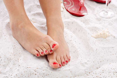 Womans feet in the sand with painted toenails Stock Photo