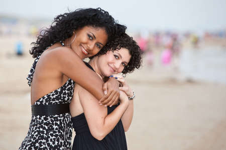 Two beautiful women on the beach in an embrace photo