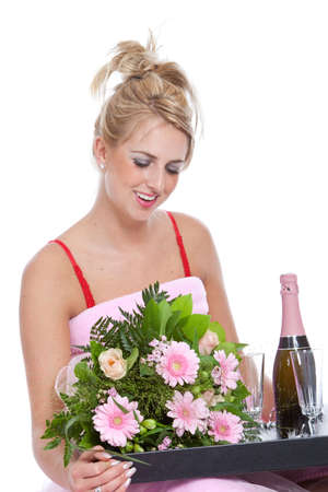 Beautiful blond girl getting a tray with flowers and champagne in bed for valentine photo