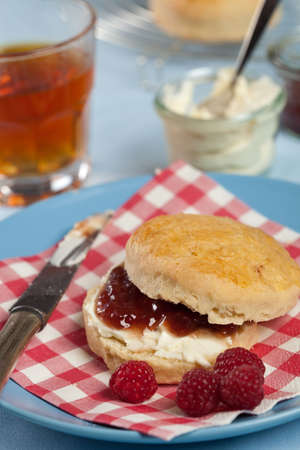 Freshly baked scones with clotted cream and raspberry jam photo