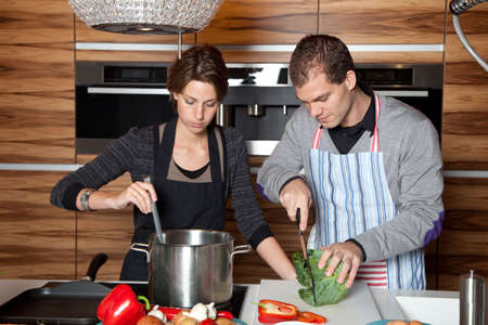 Lovely young couple working together in the kitchen photo