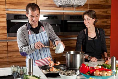 mujeres cocinando: Agregar los camarones en la sart�n de hombre Foto de archivo