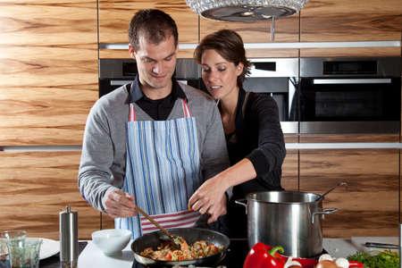hombre cocinando: Mujer alcanzar con su mano en la sart�n para degustar lo que hizo su novio