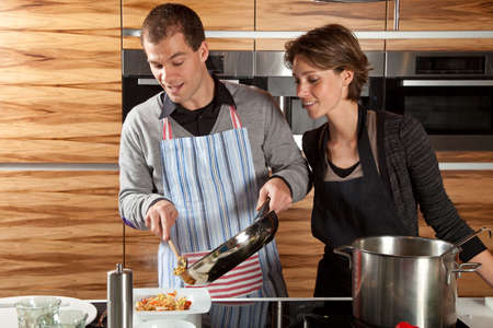 Attractive young couple cooking together in the kitchen photo