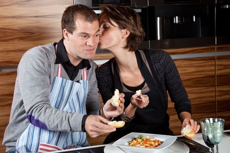 Woman planting a small kiss on her boyfriends cheek for cooking Stock Photo - 6369490