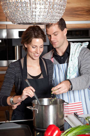 Man and woman together cooking in the kitchen, man adding something to the pan photo