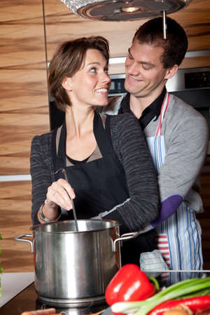 Happy young couple cooking together in the kitchen Stock Photo - 6465877