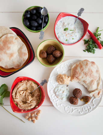 falafel: Delicious table filled with snack such as homemade pita, tzatziki, hummus and falafel