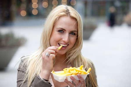 Pretty blond Girl eating Fries mit mayonnaise Standard-Bild - 6802519