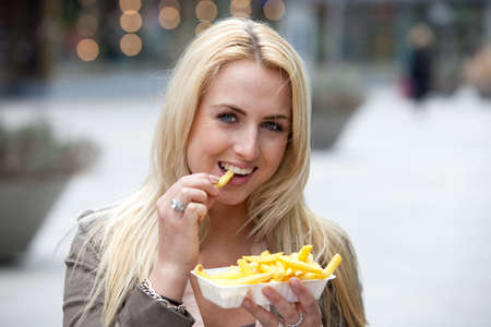 Pretty blond girl eating fries with mayonnaise photo