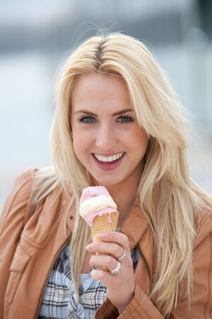 Pretty young blond girl with an icecream looking happy photo