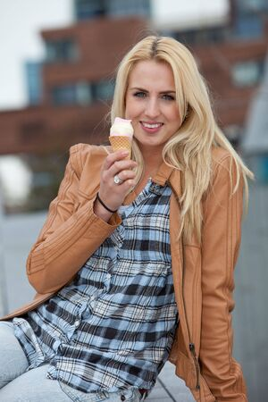 Pretty blond girl enjoying her icecream while sitting outdoors photo
