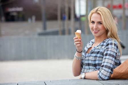 Beautiful young girl standing outdoors and eating an icecream photo
