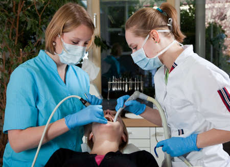 assistent: Female dentist working on her patient with her assistent