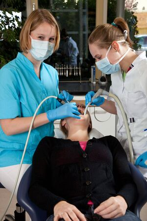 medical gloves: Dentist and her assistent working on a patient