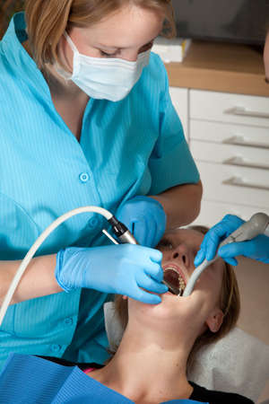 dentist drill: Female dentist drilling a cavity in her patients mouth