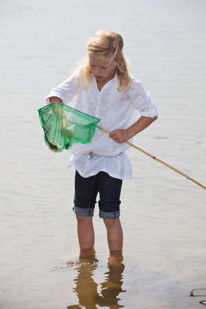 Little girl with a net to catch shrimps from the sea photo