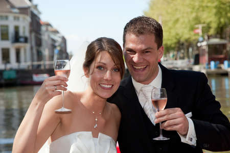 Beautiful young couple having a toast to their wedding photo