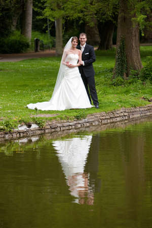 Bride and groom in the park near a pond reflecting
