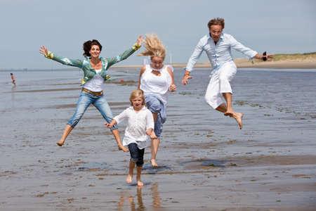 Glücklich junge Familie am Strand springen  Standard-Bild - 7874635