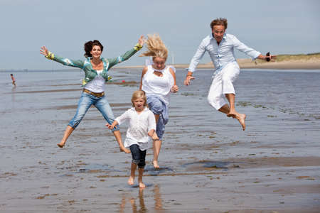 women having fun: Happy young family at the beach jumping