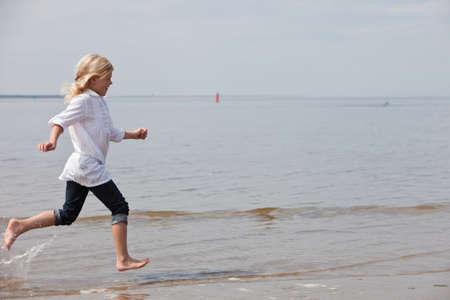 linea de flotaci�n: Ni�o corriendo a lo largo de la playa de la l�nea de flotaci�n  Foto de archivo