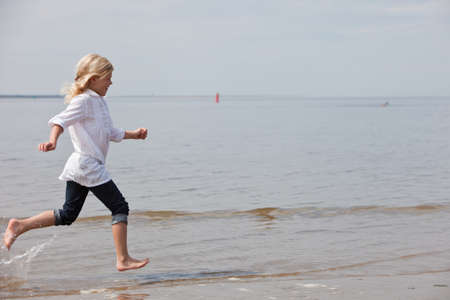 Young child running along the beach at the waterline photo