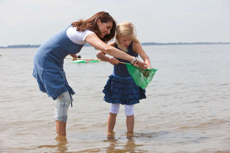 Mother and daughter checking the contents of the fishing net photo