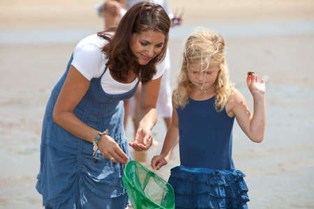 fishingnet: Mother and daughter by the seaside fishing with shrimpnet Stock Photo
