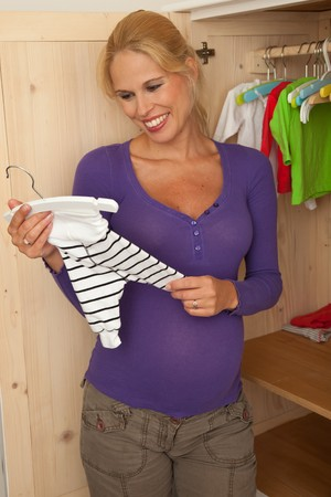 babyroom: Pregnant woman longingly looking at the tiny babyclothes, that are ready in the closet