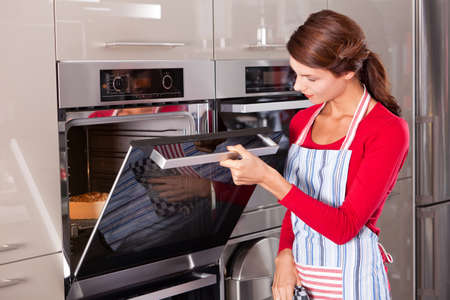 kitchen apron: Beautiful young woman checking how her cake is doing in the oven Stock Photo