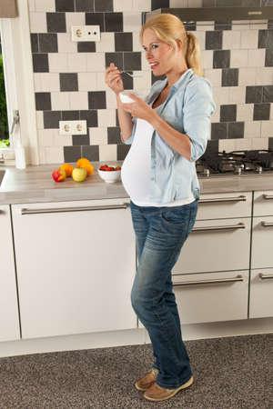 Beautiful pregnant woman having a bowl of yogurt and fruit for lunch photo