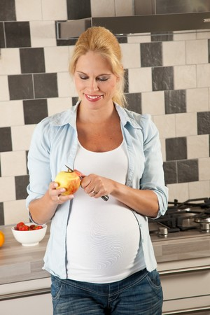 Beautiful pregnant woman standing in the kitchen peeling an apple photo