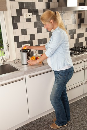 Attractive pregnant woman making orange juice for herself photo