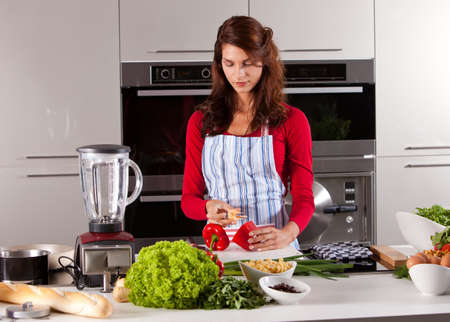 Pretty young woman cleaning the pepper in the kitchen Stock Photo - 8071163