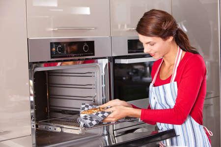 Brunette, wobei den Kuchen aus dem Ofen Standard-Bild - 8071210