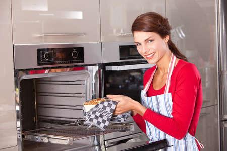 Brunette nemen haar vers gebakken cake uit de oven