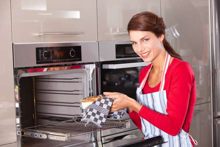 Brunette taking her freshly baked cake out of the oven