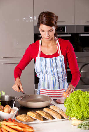 Brunette in the kitchen baking an egg Stock Photo - 8071212