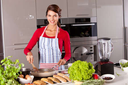 Beautiful brunette in the kitchen baking an egg and smiling photo