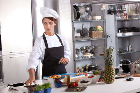 kitchen aprons: Attractive female chef working in her kitchen preparing the meal