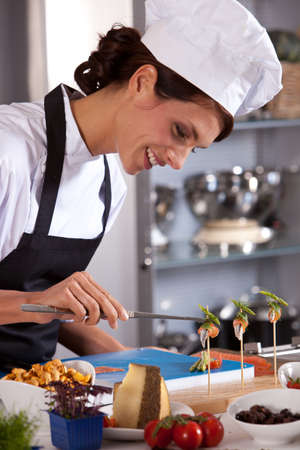 Attractive and happy female chef preparing an amuse Stock Photo
