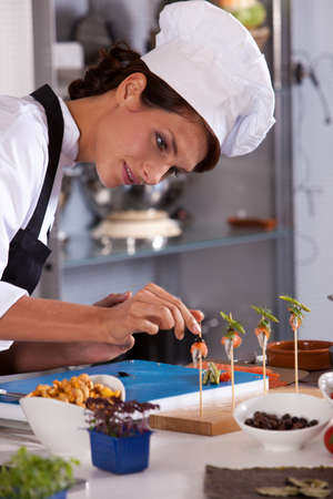 Young female chef adding the finishing touch to her amuse Stock Photo