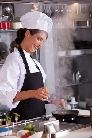 Professional chef in the kitchen adding some water to her dish Stock Photo